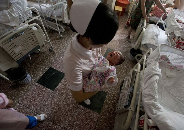 In this photo taken Thursday, July 25, 2013, a nurse holds Baby Liang in a hospital where she was born in Beijing