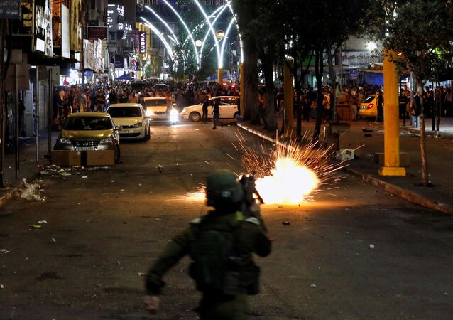 A stun grenade fired by Israeli forces explodes as Palestinians take part in an anti-Israel protest amid a flare-up of Israeli-Palestinian violence, in Hebron in the Israeli-occupied West Bank May 11, 2021.