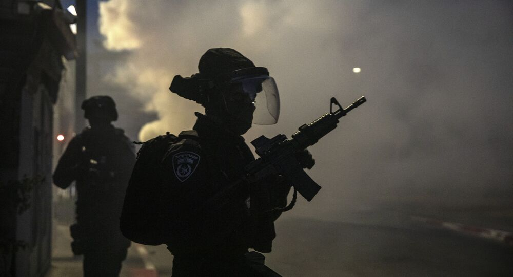 Israeli forces run during clashes with Israeli Arabs in the Israeli mixed city of Lod, Israel, Tuesday, May 11,2021.