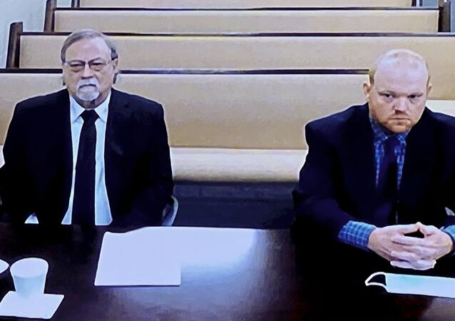 In this image made from video, from left, father and son, Gregory and Travis McMichael, accused in the shooting death of Ahmaud Arbery in Georgia on Feb. 2020, listen via closed circuit tv in the Glynn County Detention center in Brunswick, Ga., on Thursday, Nov. 12, as lawyers argue for bond to be set at the Glynn County courthouse.