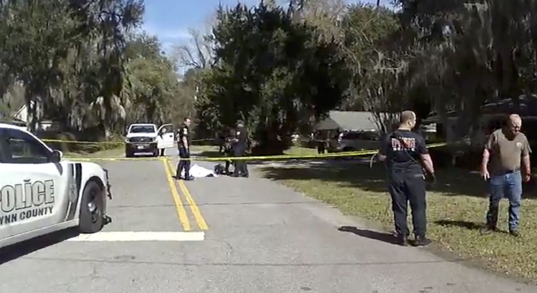 In this Feb. 23, 2020 image taken from Glynn, Ga., County Police body camera video, authorities, rear, stand over the covered body of Ahmaud Arbery, a 25-year-old Black man, who was shot and killed while while running in a neighborhood outside the port city of Brunswick, Ga.