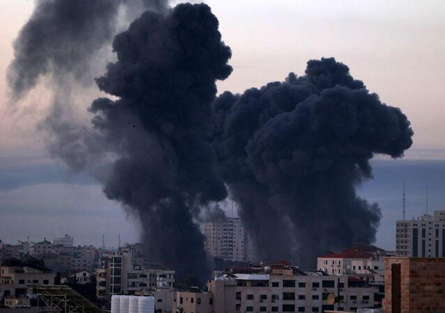 Smoke rises after an Israeli air strike in Gaza City near Barcelona Park and multiple government places, one of the biggest air strikes on the Gaza Strip, early on May 12, 2021.
