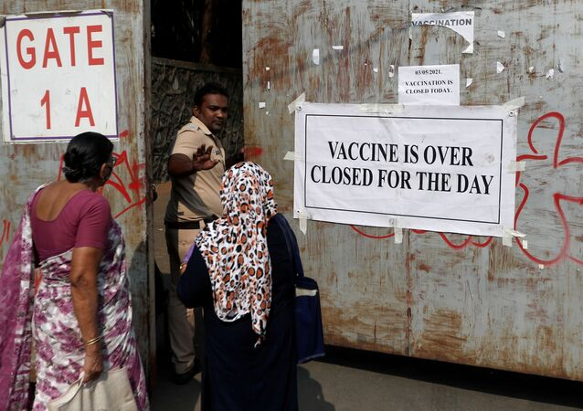 A policeman asks people who came to receive a dose of a coronavirus disease (COVID-19) vaccine to leave as they stand outside the gate of a vaccination centre which was closed due to unavailability of the supply of COVID-19 vaccine, in Mumbai, India, 3 May 2021.