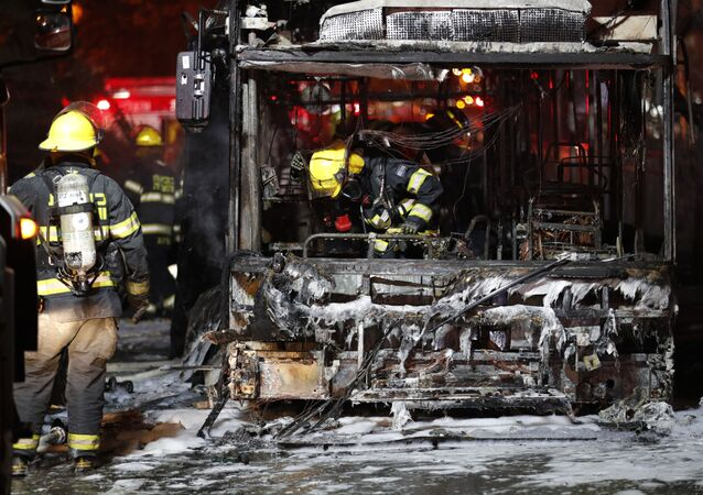 Israeli firefighters check out a burnt bus in the Israeli town of Holon near Tel Aviv, on May 11, 2021, after rockets are launched towards Israel from the Gaza Strip controlled by the Palestinian Hamas movement