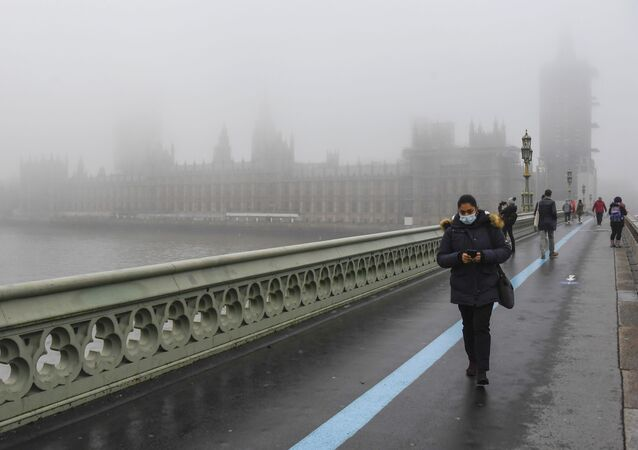 People wearing face masks, walk over Westminster Bridge with the Houses of Parliament shrouded by fog, in London, Tuesday, Dec. 8, 2020