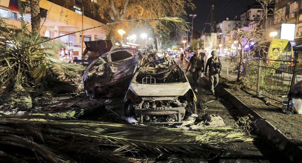Israeli security forces walk past extinguished burnt vehicles in Holon near Tel Aviv, on 11 May 2021, after rockets were launched towards Israel from the Gaza Strip, which is controlled by the Palestinian movement Hamas.