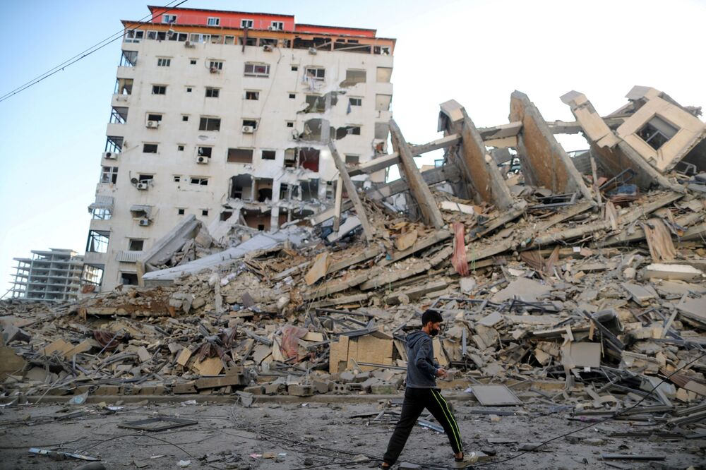 A Palestinian boy walks past the remains of a tower building which was destroyed in Israeli air strikes, amid a flare-up of Israeli-Palestinian violence, in Gaza City 12 May 2021.
