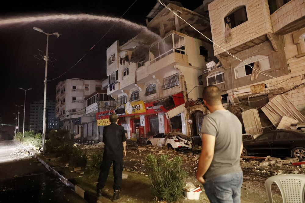 Firefighters extinguish burning apartment buildings after they were hit by Israeli airstrikes, in Gaza City, early Wednesday, 12 May 2021.