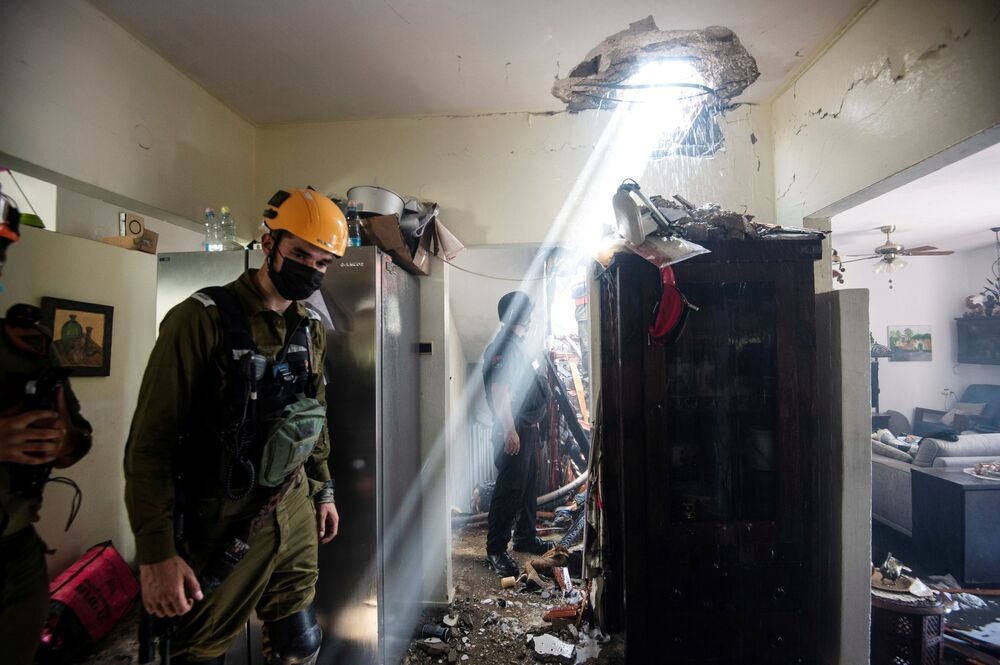 Soldiers work at a building damaged by a rocket launched from the Gaza Strip, in Ashdod, southern Israel, 11 May 2021.
