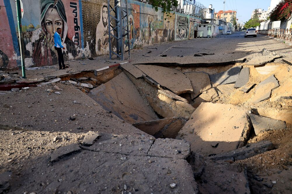 A Palestinian man stands in front of a huge crater in Gaza City early on 12 May 2021, after Israeli airstrikes overnight. Israeli air raids in Gaza Strip hit the homes of high-ranking members of the Hamas militant group, the military said Wednesday, with the territory's police headquarters also targeted.