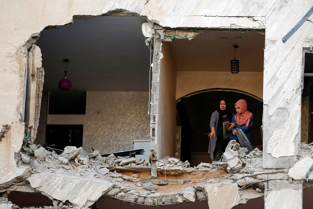 Palestinians look on as they inspect their residential building which was damaged in an Israeli air strike, amid a flare-up of Israeli-Palestinian violence, in Gaza City 12 May 2021.