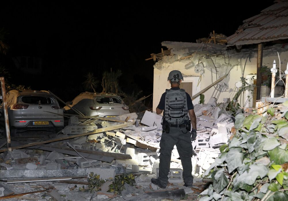 An Israeli security officer inspects damages at a house in Yehud, near Tel Aviv, on 12 May 2021, after rockets were launched towards Israel from the Gaza Strip controlled by the Palestinian militant group Hamas. Palestinian militant group Hamas said on 12 May it had fired more than 200 rockets into Israel in retaliation for strikes on a tower block in Gaza.