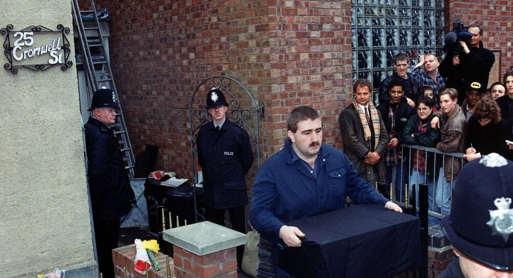 A police officer removes human remains from Fred West's former home in Gloucester in 1994.