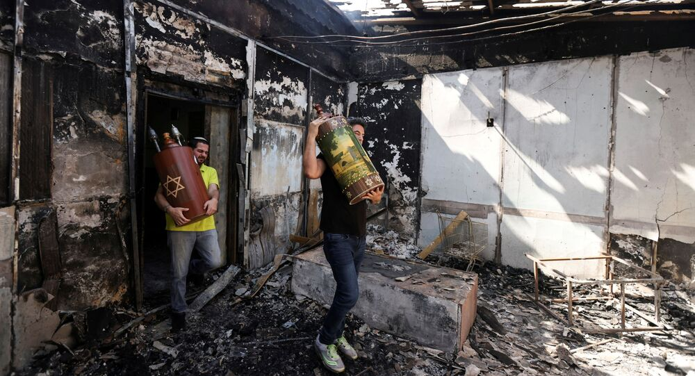 Torah scrolls, Jewish holy scriptures, are removed from a synagogue which was torched during violent confrontations in the city of Lod, Israel between Israeli Arab demonstrators and police, amid high tensions over hostilities between Israel and Gaza militants and tensions in Jerusalem May 12, 2021