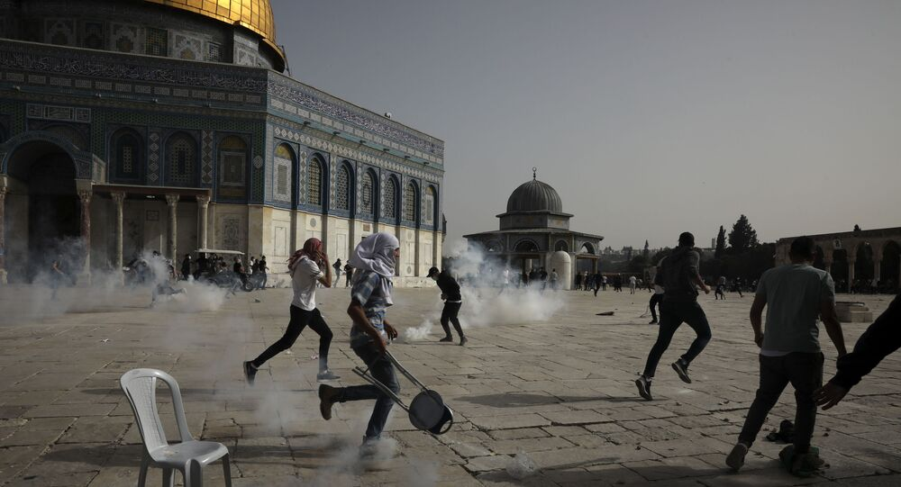 Palestinians run away from tear gas during clashes with Israeli security forces at the Al Aqsa Mosque compound in Jerusalem's Old City Monday, May 10, 2021