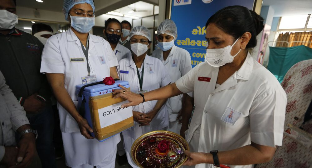 A nurse, right, performs rituals on a box containing COVID-19 vaccines upon its arrival at a government hospital in Ahmedabad, India, 16 January 2021
