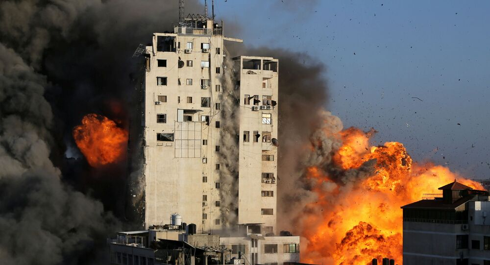 Smoke and flames rise from a tower building as it is destroyed by Israeli air strikes amid a flare-up of Israeli-Palestinian violence, in Gaza City May 12, 2021.
