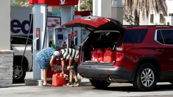 A couple fills up multiple 5 gallon gas tanks at a Wawa gas station, after a cyberattack crippled the biggest fuel pipeline in the country, run by Colonial Pipeline, in Tampa, Florida, U.S., May 12, 2021. - Sputnik International