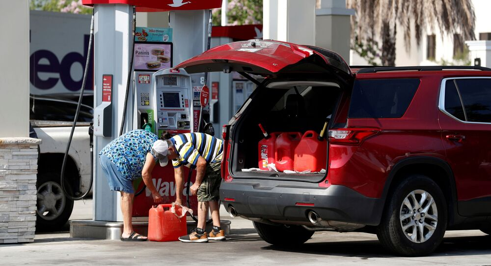 A couple fills up multiple 5 gallon gas tanks at a Wawa gas station, after a cyberattack crippled the biggest fuel pipeline in the country, run by Colonial Pipeline, in Tampa, Florida, U.S., May 12, 2021.