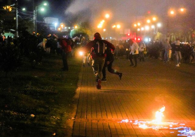 Demonstrators run while tear gas falls during a protest demanding government action to tackle poverty, police violence and inequalities in healthcare and education systems, in Bogota, Colombia, May 10, 2021.
