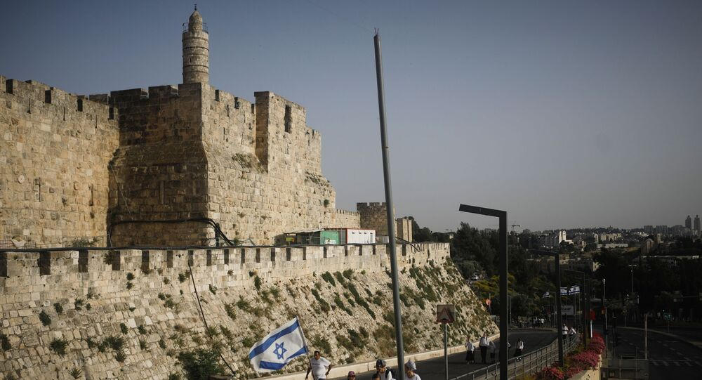 Youths wave an Israeli flag during a parade marking Jerusalem Day, amid Israeli-Palestinian tension, as they walk near the wall surrounding Jerusalem's Old City May 10, 2021. May 10, 2021.