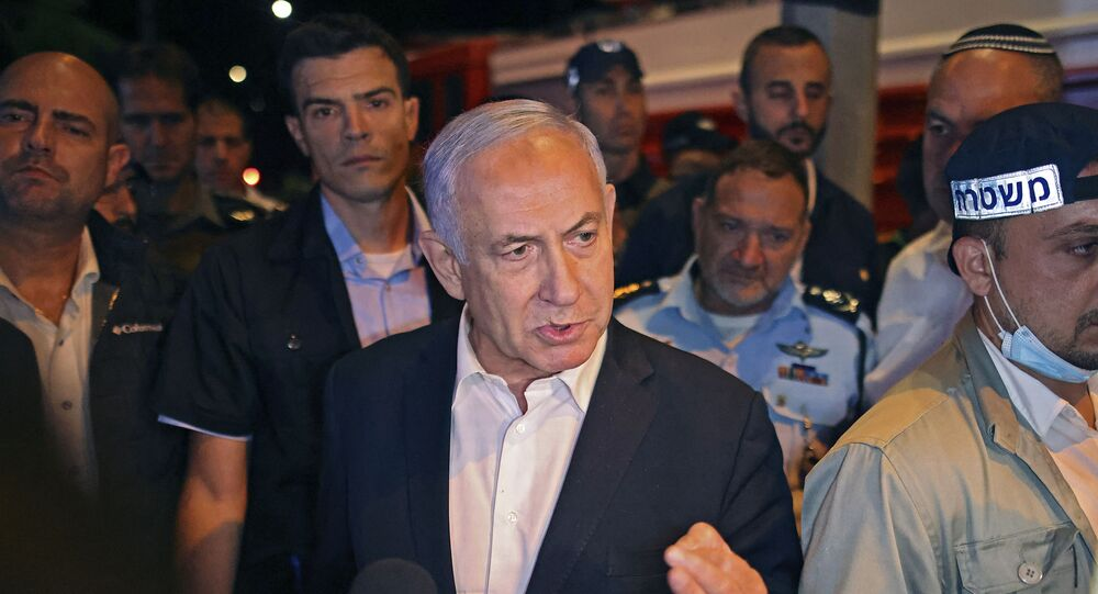 Israeli Prime Minister Benjamin Netanyahu tours the city of Lod early on May 12, 2021. - Israeli Prime Minister Benjamin Netanyahu on May 12 declared a state of emergency in the central city of Lod as police accused Arab residents of waging wide-scale riots.