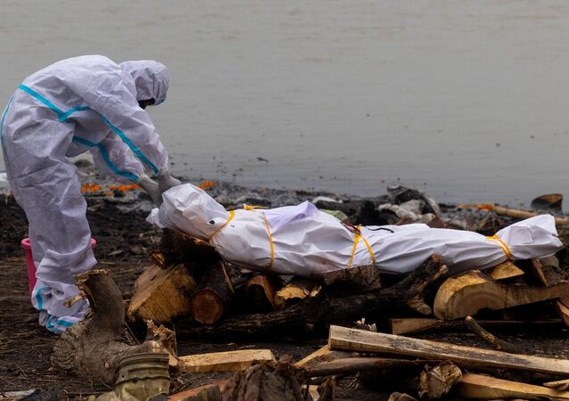A man wearing a protective suit touches the body of his relative, who died from the coronavirus disease (COVID-19), before his cremation on the banks of the river Ganges at Garhmukteshwar in the northern state of Uttar Pradesh, India, May 6, 2021.