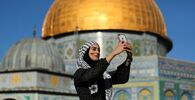 A Palestinian woman takes a selfie with the Dome of the Rock seen in the background, during Eid al-Fitr prayers, which mark the end of the holy fasting month of Ramadan. The compound houses al-Aqsa mosque, known to Muslims as Noble Sanctuary and to Jews as Temple Mount, in Jerusalem's Old City, as Israel and Gaza continue their fighting on 13 May 2021.