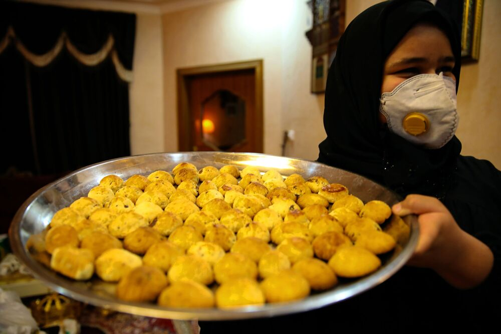 An Iraqi woman carries biscuits during the first day of the Eid al-Fitr holiday in Basra, Iraq, on Thursday 13 May 2021.
