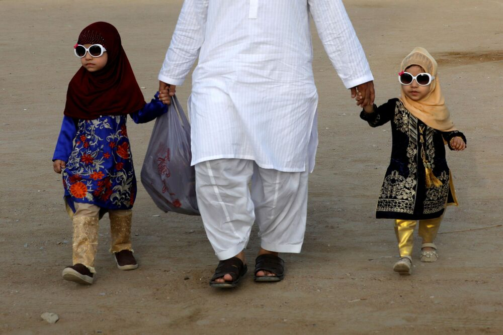 A father and his children walk together after celebrating Eid al-Fitr prayers as the outbreak of the coronavirus disease (COVID-19) continues in Karachi, Pakistan, on 13 May 2021.