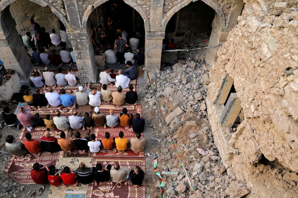 People attend Eid al-Fitr prayers on 13 May 2021 marking the end of the holy fasting month of Ramadan, at the Al-Masfi mosque - the oldest mosque in Mosul, Iraq, dating back to AD640 - which was damaged during the war against Islamic State militants.