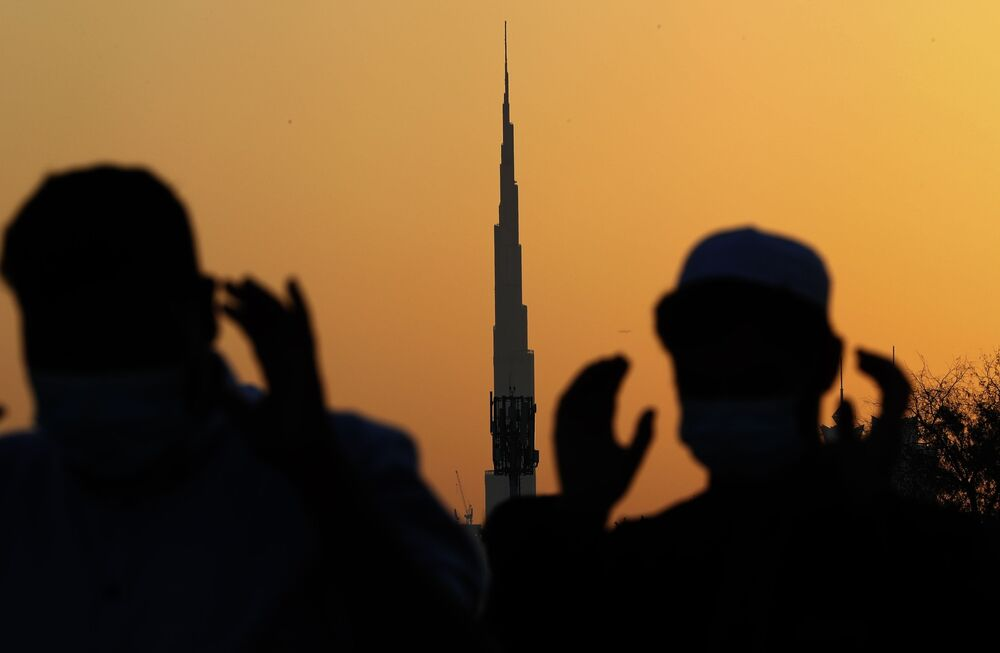 With the world's tallest building, Burj Khalifa, in the background, Muslim men wearing masks to observe coronavirus restrictions, perform Eid al-Fitr prayers marking the end of the holy fasting month of Ramadan in Dubai, United Arab Emirates, on Thursday 13 May 2021.