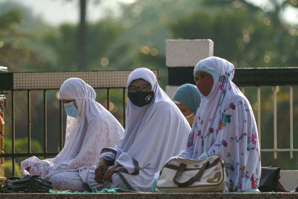 Muslim women wearing protective masks wait to pray outside the National Mosque while celebrating Eid al-Fitr in Kuala Lumpur, Malaysia, on Thursday 13 May 2021.