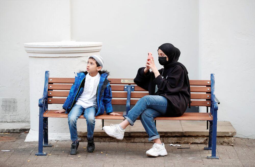 Mooosa and Tabarek Khan sit on a bench near an Eid market ahead of Eid al-Fitr celebrations in St Albans, Britain, on 11 May 2021.