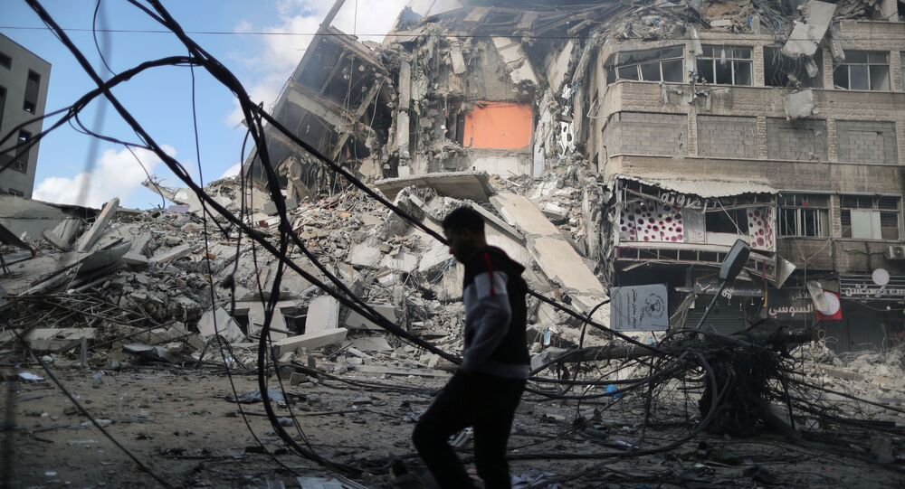 A Palestinian man walks past the remains of a tower building which was destroyed in Israeli air strikes, amid a flare-up of Israeli-Palestinian violence, on the first day of the Eid al-Fitr holiday in Gaza City, 13 May 2021
