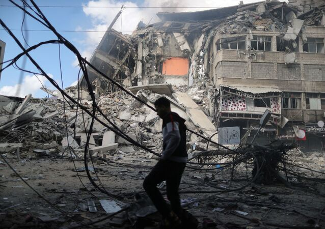 A Palestinian man walks past the remains of a tower building which was destroyed in Israeli air strikes, amid a flare-up of Israeli-Palestinian violence, on the first day of Eid al-Fitr holiday, in Gaza City May 13, 2021