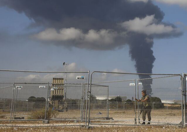 An Israeli soldier stands guard next to an Iron Dome air defense system as smoke rises from an oil tank on fire after it was hit by a rocket fire from Gaza Strip, near the town of Ashkelon, Israel,, Wednesday, May 12, 2021
