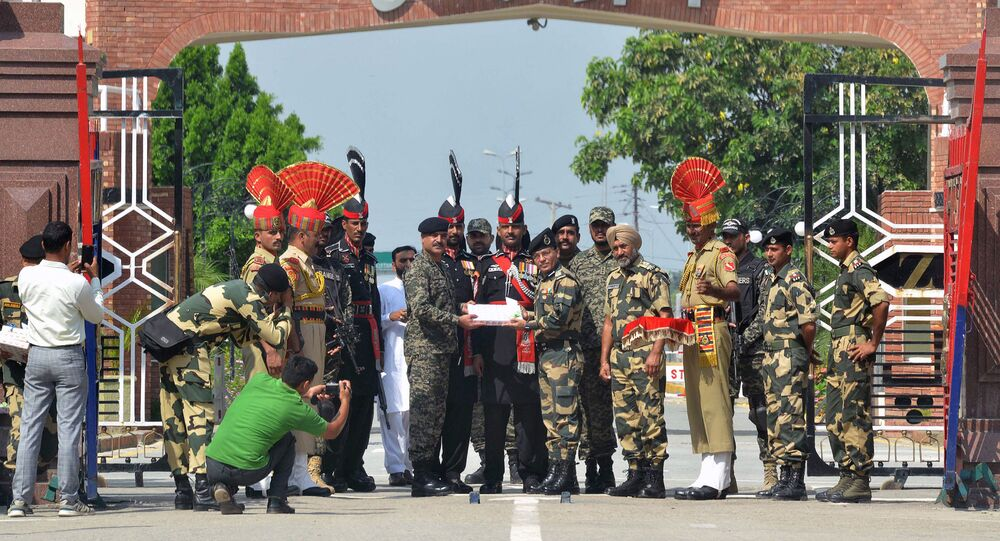 Indian Border Security Force (BSF) commandant Sudeep (centre R) presents sweets to Pakistani Wing Commander Bilal (centre L) on the occasion of the Eid al-Adha festival at the India-Pakistan Wagah border post on September 2, 2017