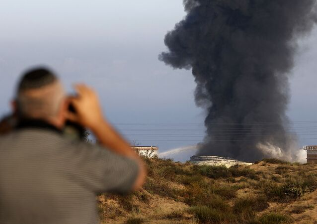 An Israeli man watches from a distance as smoke billows early on May 12, 2021 from Ashkelon's refinery, hit by Hamas rockets the previous day, in the southern Israeli city, near the Gaza Strip