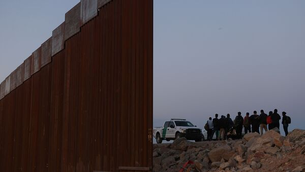 Asylum seekers are detained by U.S. Border Patrol at the border wall after crossing into the United States near Yuma - Sputnik International