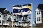 An advertising sign for building land stands in front of a new home construction site in Northbrook, Ill., Sunday, March 21, 2021.