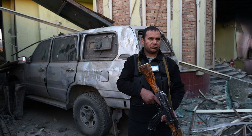 An Afghan security official stands alert among damaged buildings and a vehicle after a car bomb attack near the Spanish embassy compound in Kabul on December 12, 2015