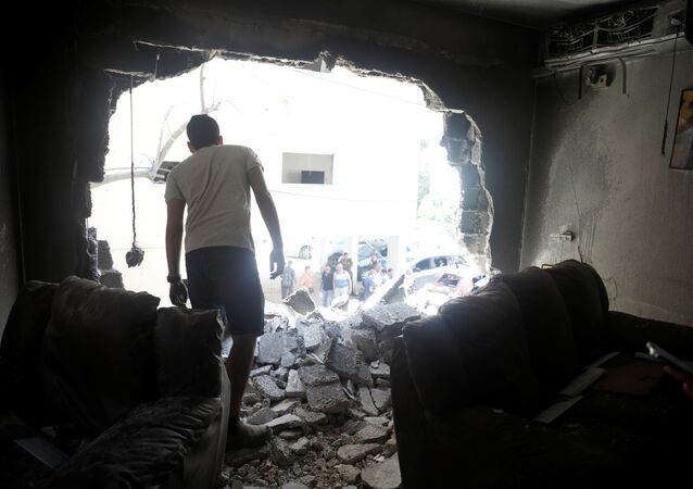 A man stands atop rubble as he surveys the damage after a rocket launched overnight from the Gaza Strip hit a residential building in Petah Tikva, Israel May 13, 2021