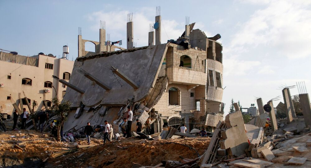 Palestinians gather around the ruins of buildings which were destroyed in Israeli air strikes amid a flare-up of Israeli-Palestinian violence, in the northern Gaza Strip May 13, 2021.