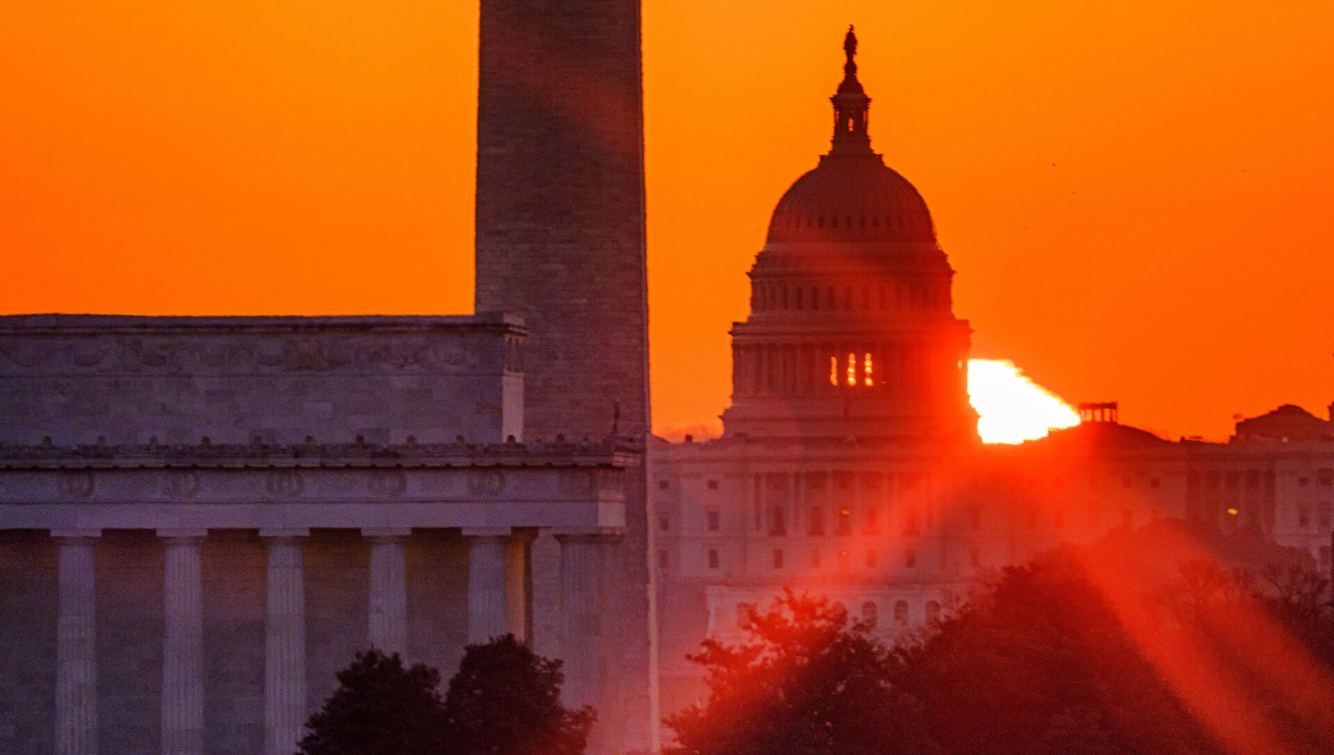 The sun flares through the camera lens as it rises behind the U.S. Capitol building, Washington Monument and the Lincoln Memorial, Monday, March 22, 2021, in Washington. - Sputnik International, 1920, 31.07.2021