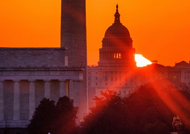The sun flares through the camera lens as it rises behind the U.S. Capitol building, Washington Monument and the Lincoln Memorial, Monday, March 22, 2021, in Washington.