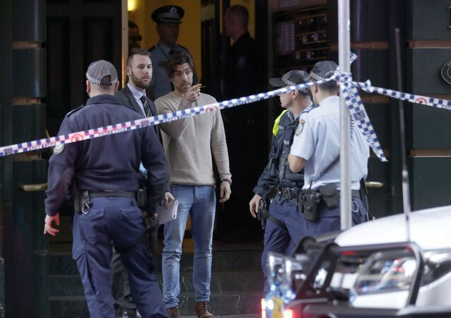 A man, center, points as he assists police at a building where a person has been found deceased after a man attempted to stab multiple people in Sydney, Australia, Tuesday, Aug. 13, 2019