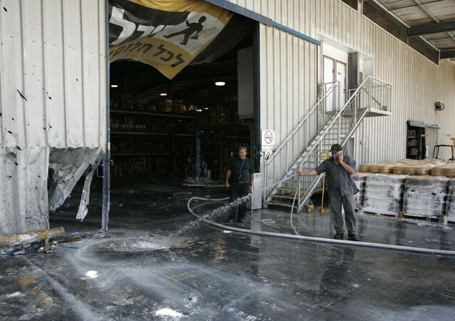 An Israeli worker uses a hose to clean at the scene  where a mortar fired by Palestinian militants in Gaza hit a factory in the southern Israeli kibbutz of Nir Oz, 5 June 2008