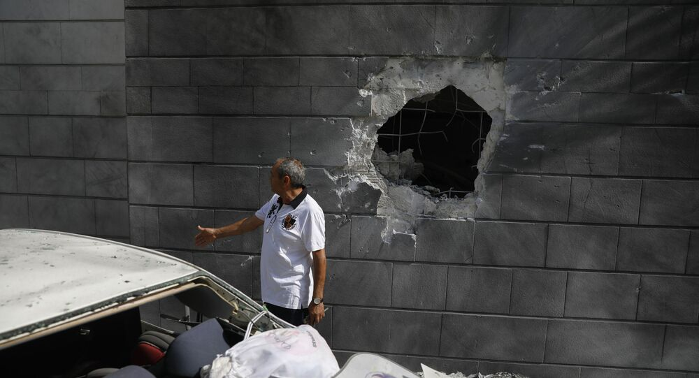 A man inspects the damaged wall of a residential building that was hit by a rocket fired from the Gaza Strip in Ashkelon, Israel, Friday, May 14, 2021.