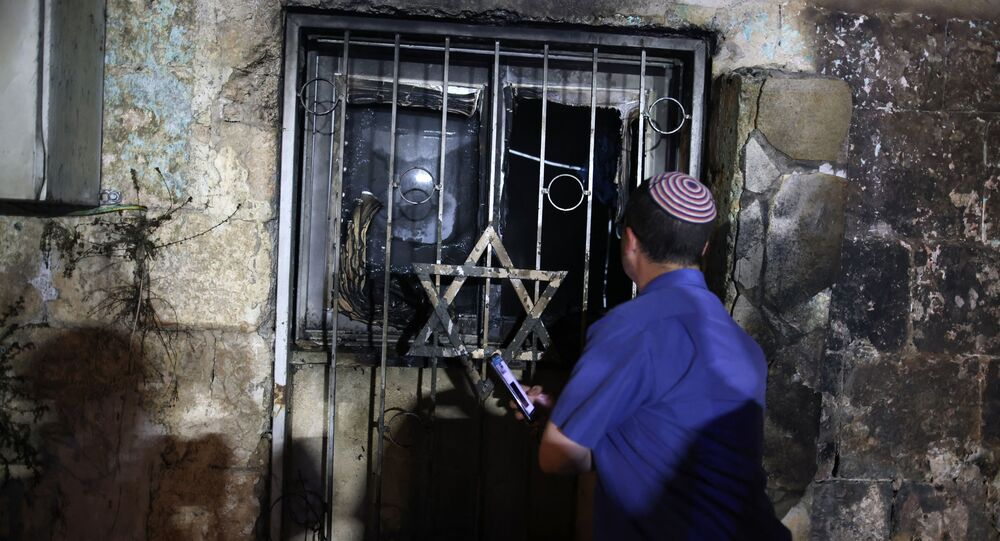 An Israeli man looks inside a synagogue after it was set on fire by Arab-Israelis, in the mixed Jewish-Arab city of Lod on 14 May 2021, during clashes between Israeli far-right extremists and Arab-Israelis
